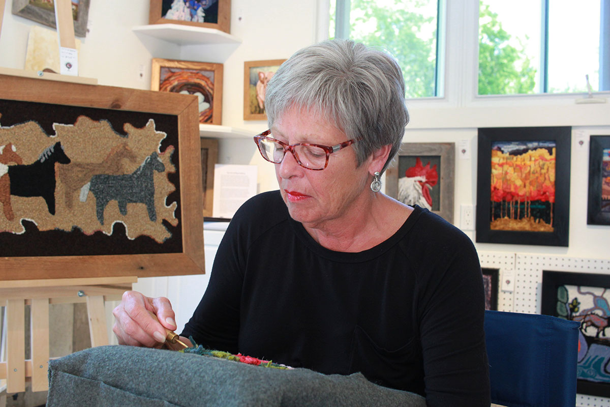 Laurie McRae hooking in her studio